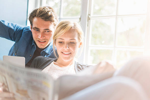 young couple reading magazine by window at home - woman home magazine stockfoto's en -beelden