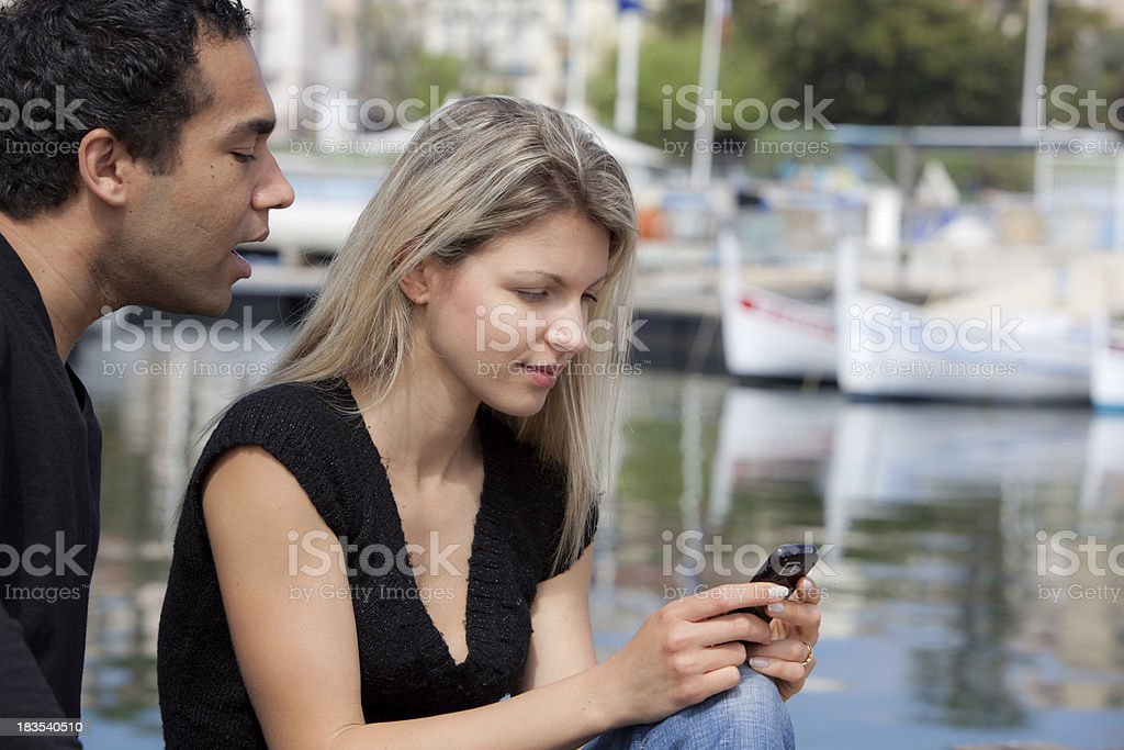 Young couple reading text message on mobile phone stock photo