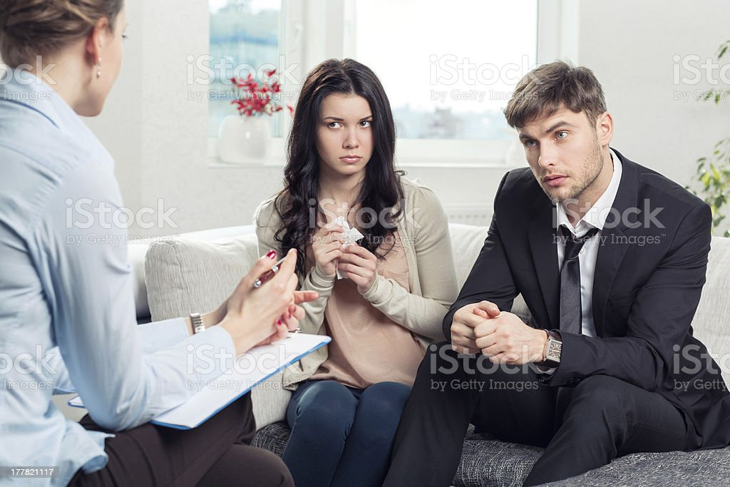 Young couple receiving advice at a psychologist office stock photo