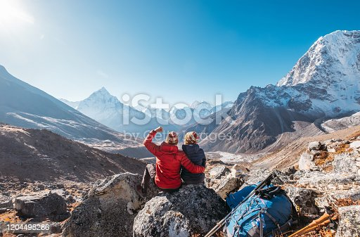 Young couple rejoicing on Everest Base Camp trekking route near Dughla 4620m. Backpackers left Backpacks and trekking poles and enjoying valley view with Ama Dablam 6812m peak and Tobuche 6495m