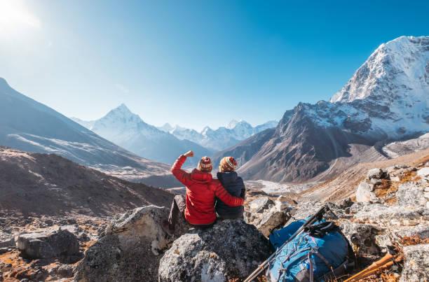Pareja joven regocijándose en la ruta de senderismo Everest Base Camp cerca de Dughla 4620m. Los mochileros dejaron mochilas y bastones de trekking y disfrutan dotadas de vistas al valle con el pico Ama Dablam 6812m y Tobuche 6495m - foto de stock