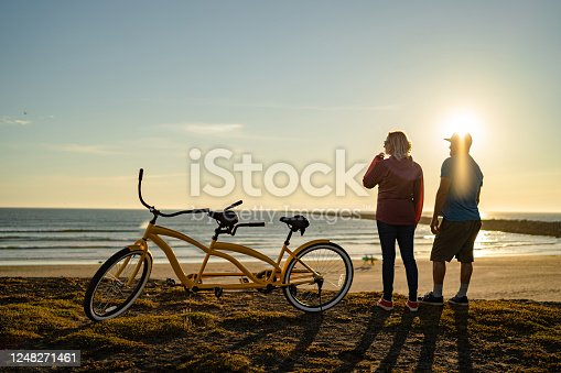 They stand beside their parked tandem bike, Pacific Ocean in distance