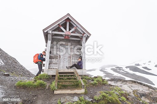 A millennial couple relax at a one-room cabin rest stop partway up the glacier they're climbing. A snowy mountain range is in the background. He is standing by the railing, she is sitting on the porch.