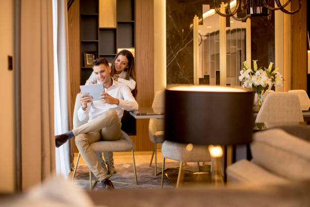 Young couple relaxing at luxurious home with digital tablet stock photo
