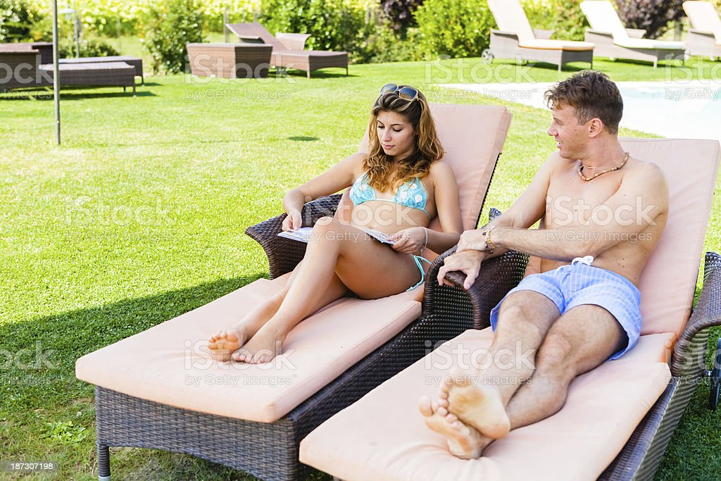 Young Couple Relaxing by the Pool during Holidays royalty-free stock photo
