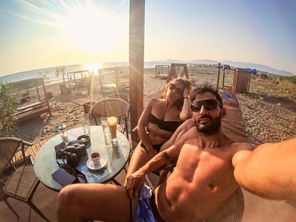 pareja joven relajándose en el club de playa en montenegro - happy couple sharing a cup of coffee fotografías e imágenes de stock