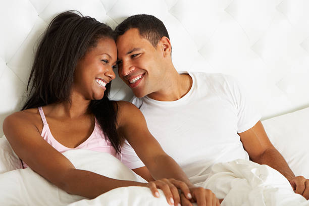 A young couple relaxing in bed together stock photo