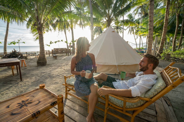 Young couple relaxing in glamping campground in tropical scenery stock photo