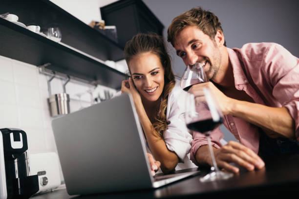 Junges Paar entspannen in der Küche mit Wein und Laptop. Liebe, Technik, Menschenkonzept. – Foto