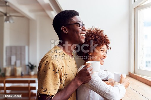Young Couple Relaxing In Loft Apartment Looking Out Of Window With Hot Drink