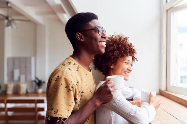 joven pareja relajante en apartamento tipo loft mirando fuera de ventana con bebida caliente - café bebida fotografías e imágenes de stock