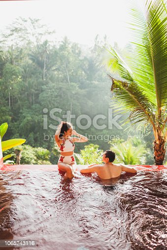 istock Young couple relaxing in luxury private infinity pool with amazing jungle view from above in Bali 1065243116