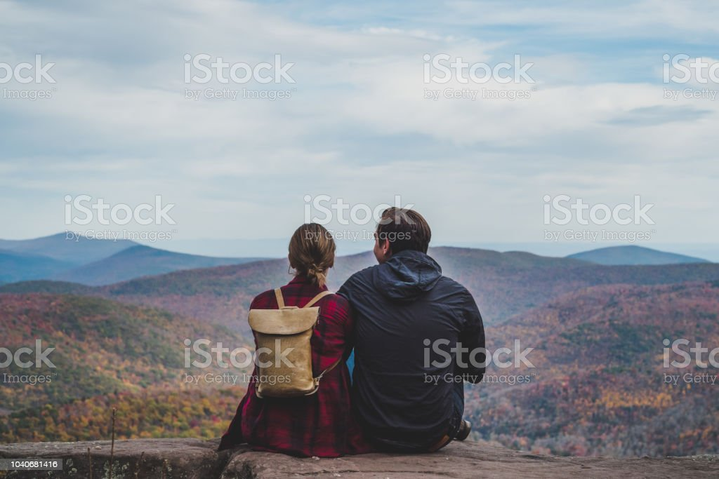 A Young Couple Relaxing in nature in Autumn A beautiful shot of a couple relaxing in nature in autumn when the colors are changing. Adult Stock Photo