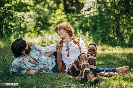 Two people, man and woman, hippie couple relaxing on grass in nature together.
