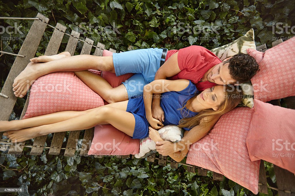 Young couple relaxing on a garden hammock stock photo