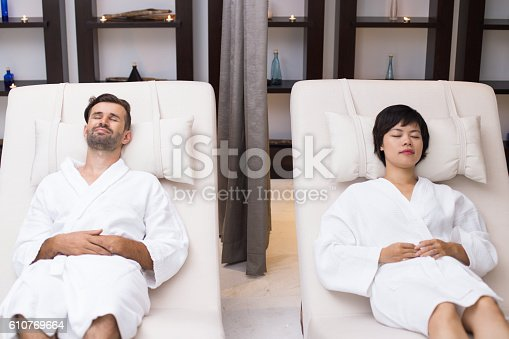 610769340istockphoto Young Couple Relaxing on Loungers in Spa Center 610769664