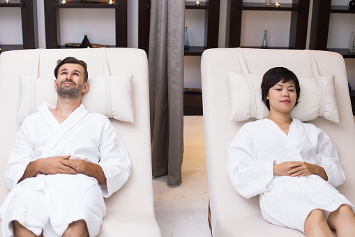 610769340 istock photo Young Couple Relaxing on Loungers in Spa Salon 610769728