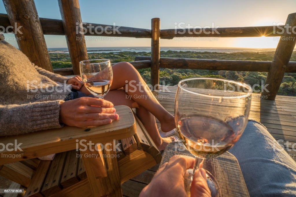 Young couple relaxing on terrace at sunset stock photo