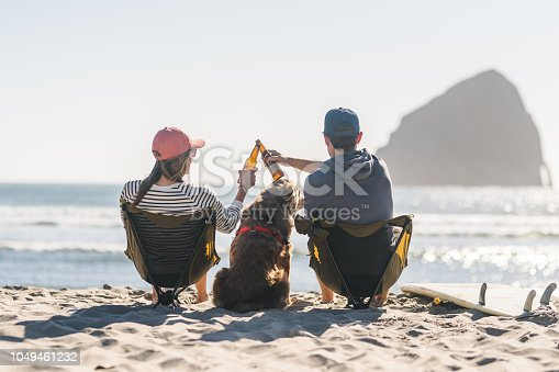 A couple relax on a sandy beach with their beer and mid-sized dog, who is sprawled in between them. Their surfboards are lying beside them and they're clinking their bottles together in a celebratory toast as they watch the ocean waves roll in. The shot is from behind.