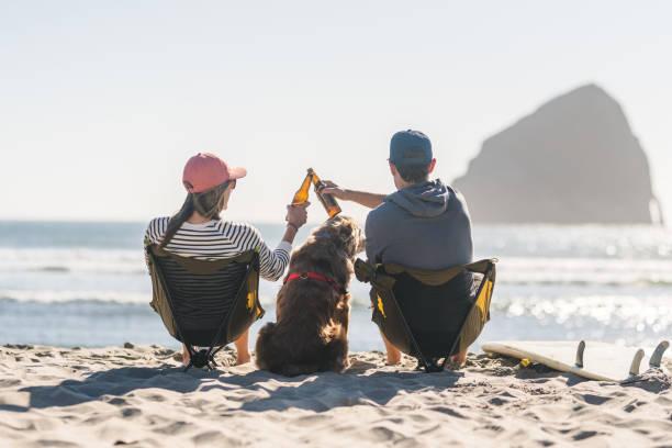 ein junges paar, die mit ihrem hund am strand entspannen - bier gesund stock-fotos und bilder
