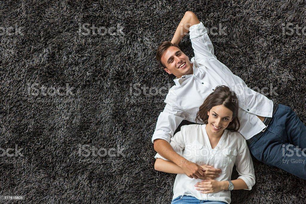 Pareja joven relajante en la alfombra - foto de stock