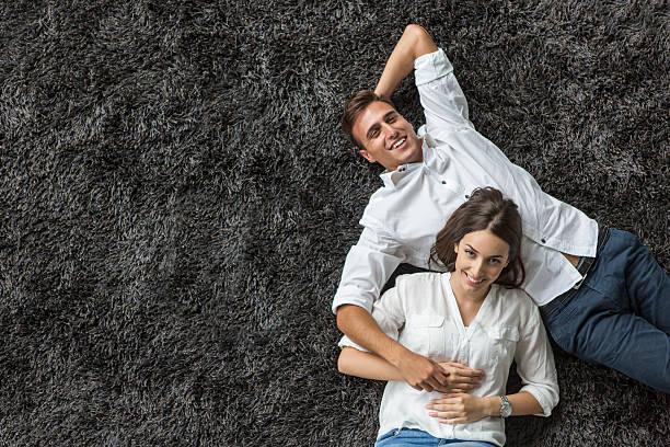young couple relaxing on the carpet - tapijt stockfoto's en -beelden