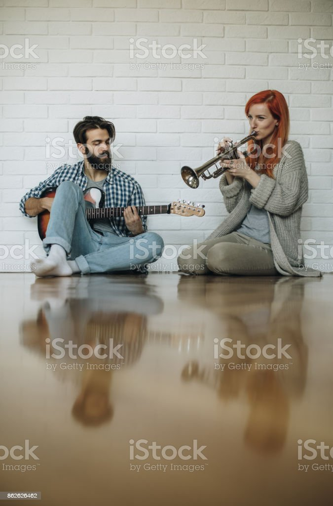 Young couple relaxing on the floor and playing musical instruments. stock photo