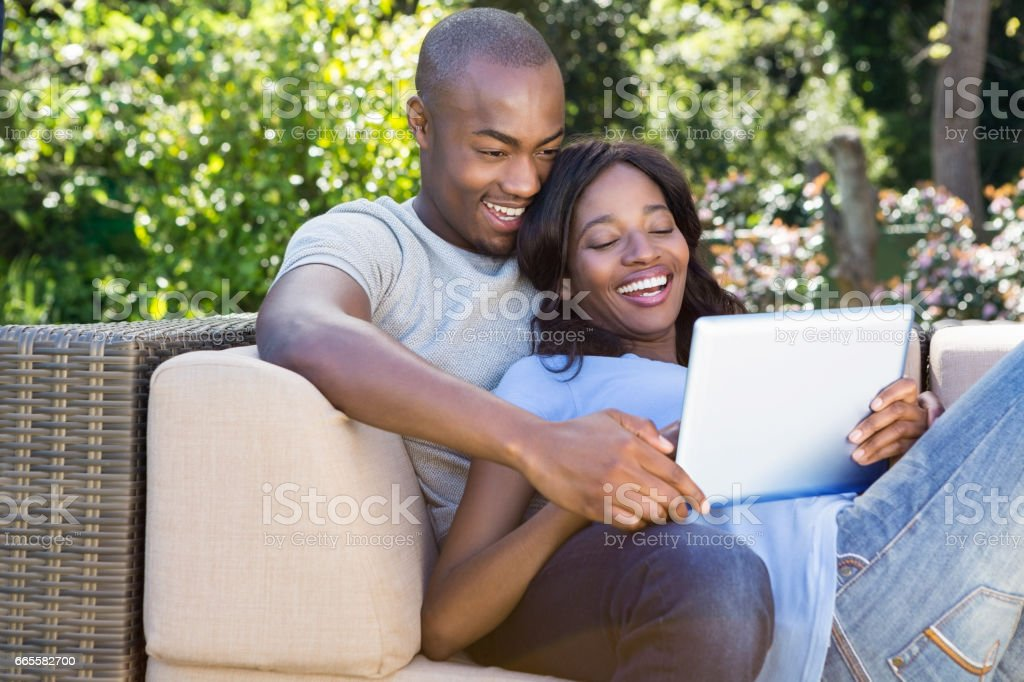 Young couple relaxing on the sofa and using digital tablet stock photo