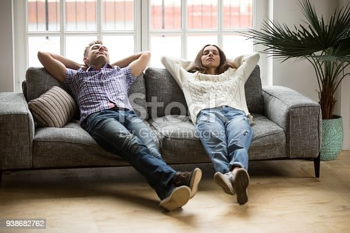 938682762istockphoto Young couple relaxing together on sofa enjoying nap breathing air 938682762