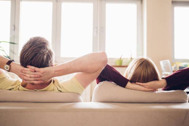 giovane coppia a riposo a casa - mani dietro la testa foto e immagini stock