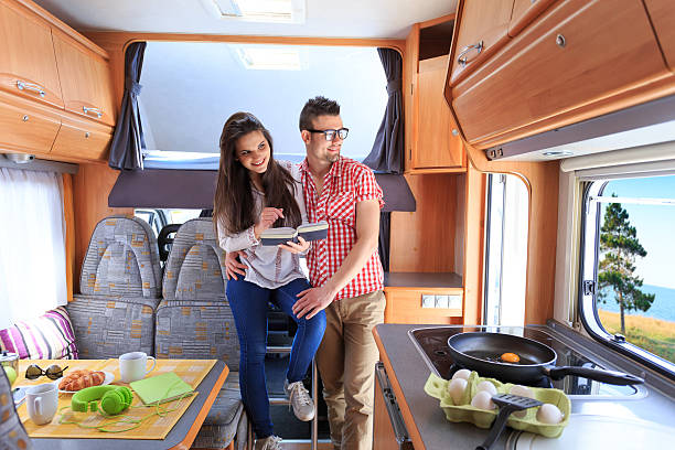 Young couple resting in caravan Smiling couple resting inside of a caravan. Girl holding a book, boy with eyeglasses standing behind her, both looking through window. On foreground table with food and coffee cups, stove, pan, peel eggs. rv interior stock pictures, royalty-free photos & images