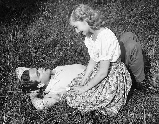Young couple resting on lawn, (B&W) stock photo