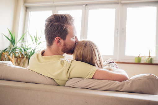 973962076 istock photo Young couple rests at home, man kissing woman on the head 969445596