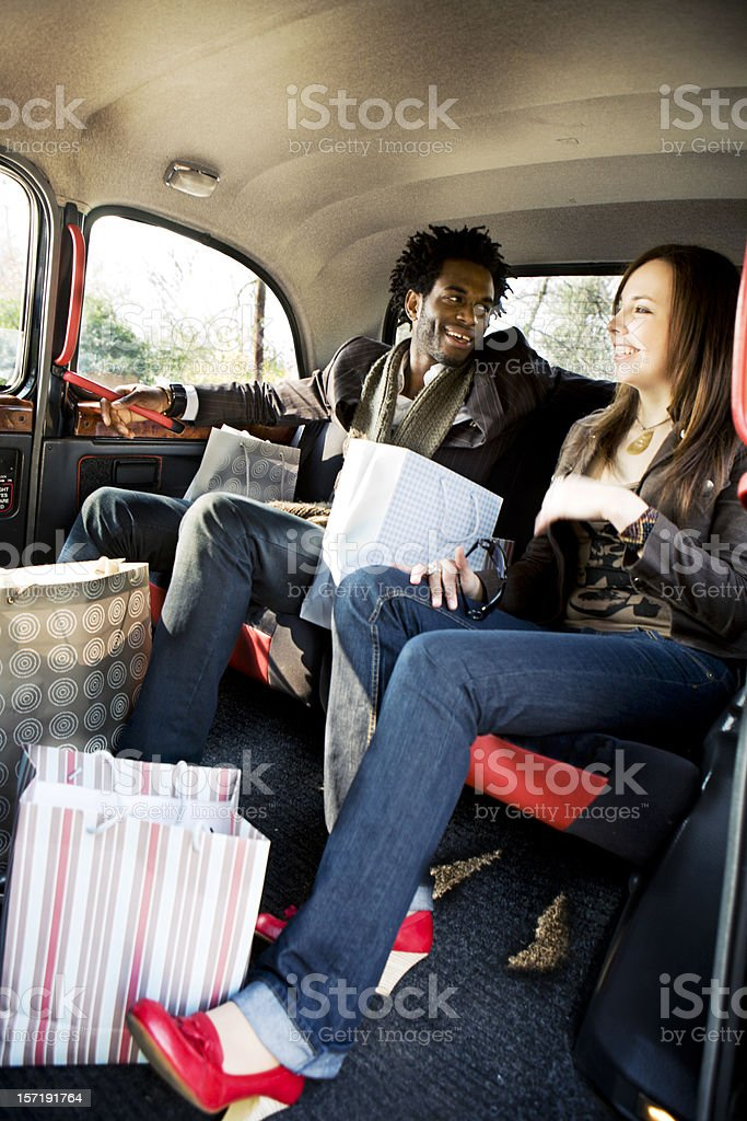 Young couple returning home in a London taxi after shopping stock photo