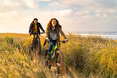 istock Young couple ride fat bikes on coastal trail 1248264659