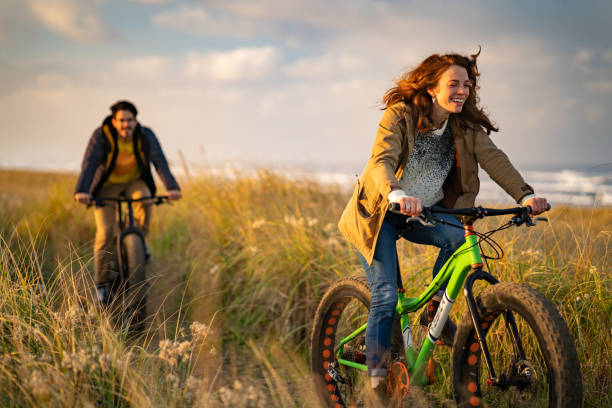 Young couple ride fat bikes on coastal trail stock photo