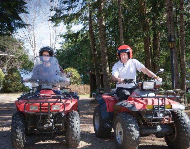 young couple riding a quad stock photo