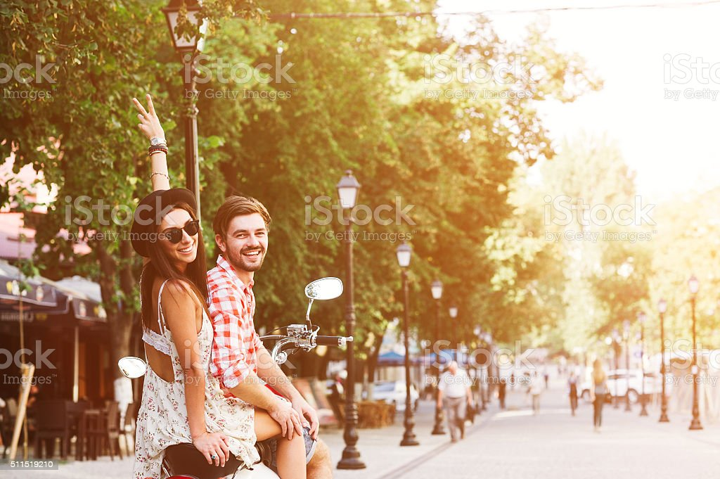 young couple riding  a vintage scooter in the street stock photo