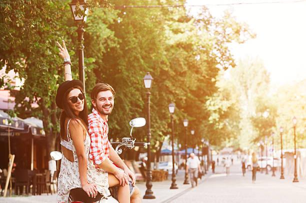 pareja joven montando un vespa vintage en la calle - vintage vespa fotografías e imágenes de stock