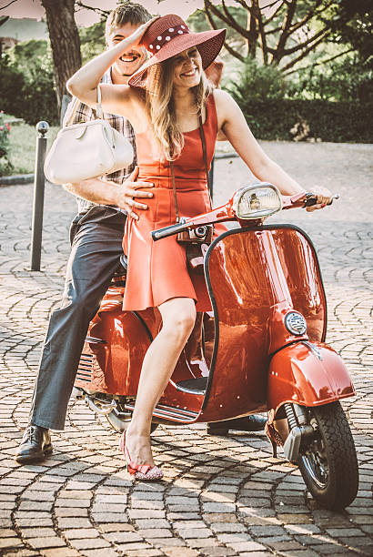 young couple riding a vintage scooter - red hutgesellschaft stock-fotos und bilder