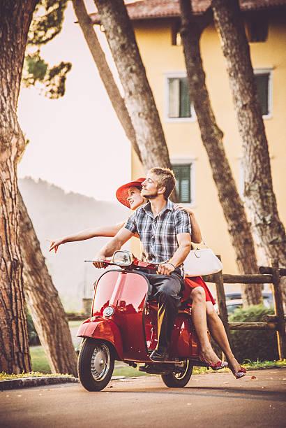 young couple riding a vintage scooter - vintage vespa fotografías e imágenes de stock