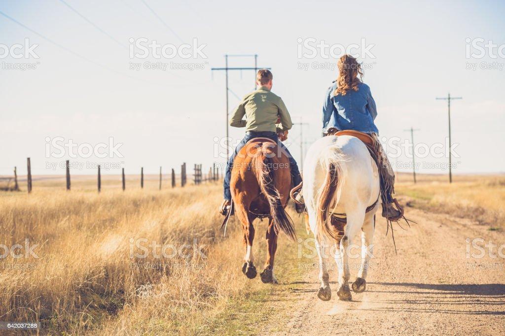 Young Couple Riding Away On Horseback stock photo