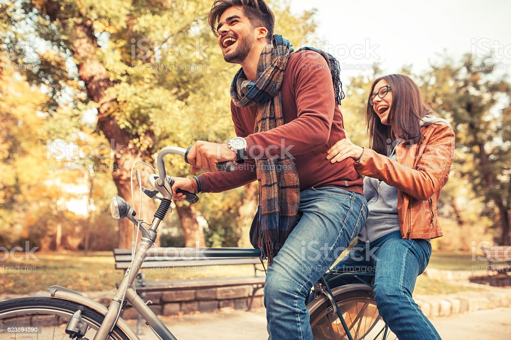 Young couple riding bicycle outdoors on street. - foto de acervo