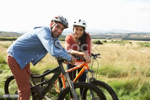 istock Young couple riding bicycles in the countryside 465140289