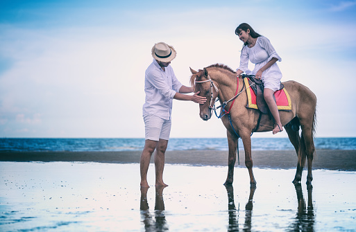 Young couple riding horse on seacoast