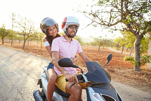 jeune couple riding scooter sur route de campagne - moped photos et images de collection