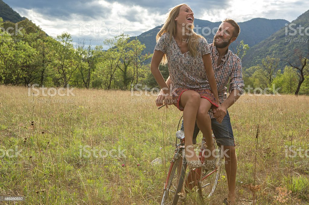 Young couple riding on a vintage bicycle in the countryside stock photo