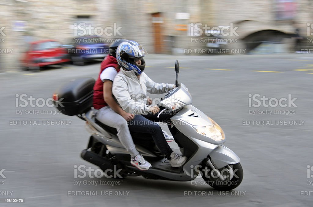 Young couple riding scooter in Siena, Italy stock photo