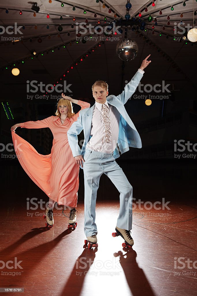 Young couple roller skating, 70s style disco fever stock photo