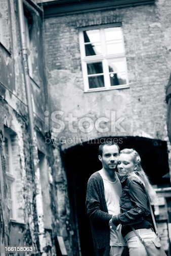A young adult Caucasian couple standing in a romantic hug in a lovely alley, the woman looking at the camera. Blue toned monochrome.